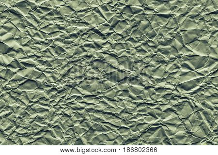 the old crumpled sheet of paper of green color for the abstract textured background and for wallpaper
