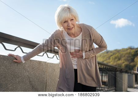 Suffering from awful pain. Middle-aged upset diseased lady expressing negative emotions standing near the fence while having stomachache
