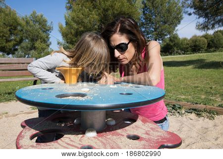 Mother And Child Playing With Sand At Playground