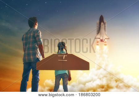 Dad and daughter watching how to fly a spaceship. Happy family on sunset background on nature.