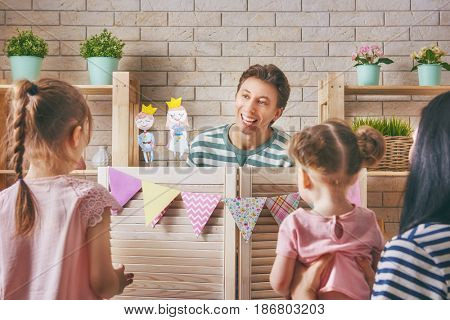 Happy loving family. Father, mother and their daughters in kids room. Funny dad, mom and lovely children having fun and playing performance in the puppet theater indoors. Prince and princess.