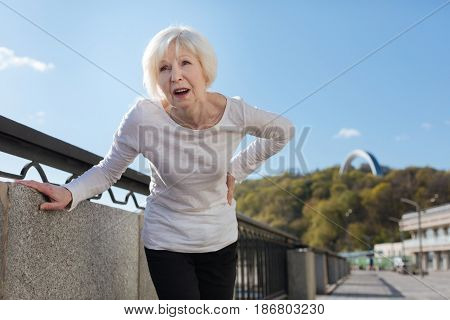 Hurry to live. Elderly beautiful stylish lady suddenly being hurt and touching her back while walking around