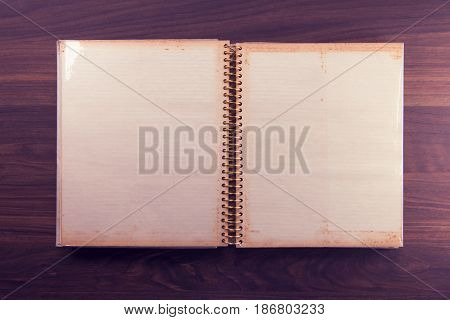Blank page of an 1970s photo album, in muted retro tone, on a dark colored wooden table.