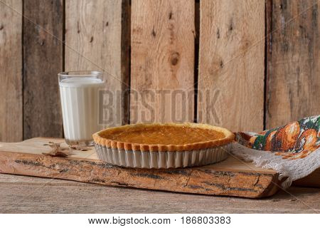 Fresh Homemade Pumpkin Pie made for Thanksgiving. Pie on a wooden background. Rustic. Country style.
