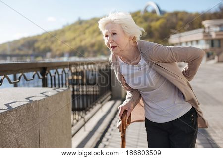 Think about your health every day. Troubled gloomy aged lady holding the hand behind the back and concerning the pain while looking far away