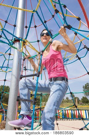 Smiling Woman Hanging In Rope Ladder