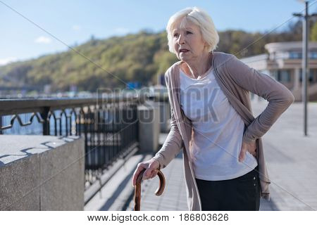 Challenges of old age. Exhausted weak neat lady feeling terrible pain in her back while resting and walking in the city