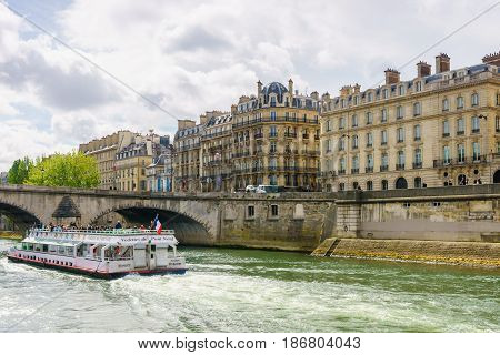 Paris France - May 1 2017: Tourists are cruising on the Seine river. To see the beautiful ancient architecture along the river on a cloudy day on May 1 2017 in Paris France.