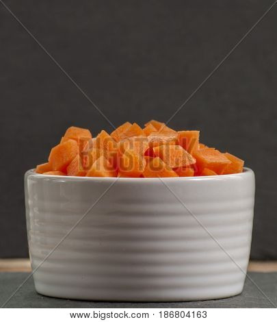 bowl sliced carrots over black cutting board