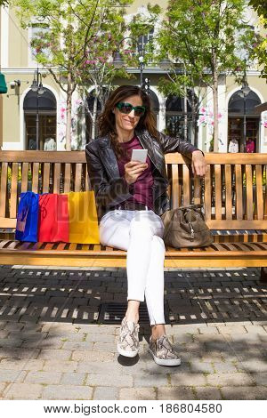 Woman In Bench With Shopping Bags Watching Mobile Vertical