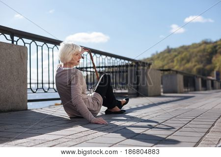 Difficultness of old age. Ill exhausted aged women experiencing pain in her legs while sitting on the ground and waiting for help