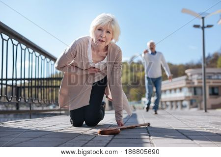 Everything can happen suddenly. Scared puzzled old woman resting and feeling heart attack while aged man running to help her