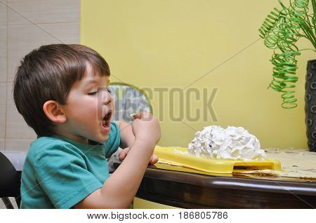 Boy eating cream  from a cake with fingers. Silly boy eat a cake