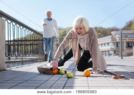 Weakness reason for troubles. Pleasant grey headed sad lady kneeling on the ground clamping greengrocery while middle-aged man going to her