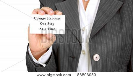 Inspiring motivation quote handwritten on a business card change happens one step at a time. White business card image.