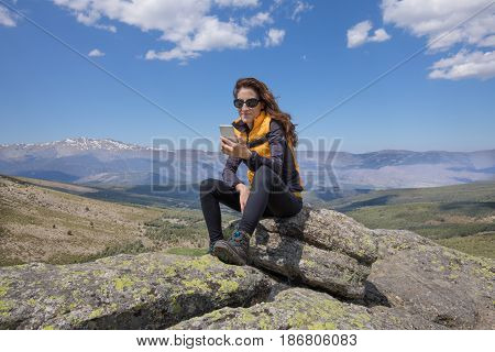 Woman Using Mobile On Top Of Mountain