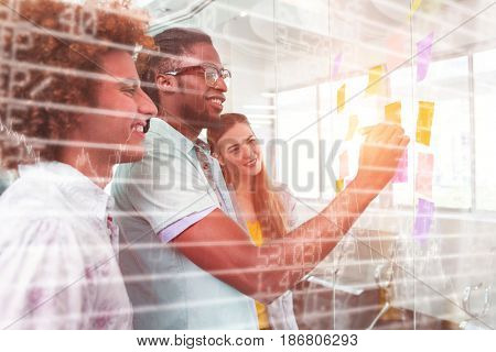 Stocks and shares against creative bussiness people discussing over adhesive notes
