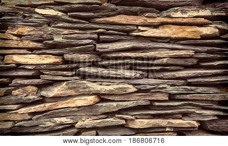 Background wall made of stone. A wall of flat stones laid in several rows