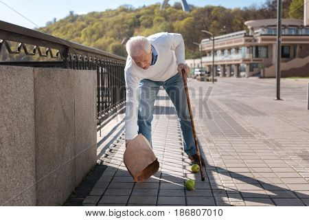 Useful vitamins for health. Befogged ordinary retired man carrying fruits home while stumbling and tripping package