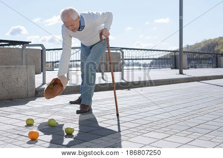 Unpleasant situation. Grey headed neat handsome pensioner going to his wife while expressing strong pain and spilling fruits everywhere