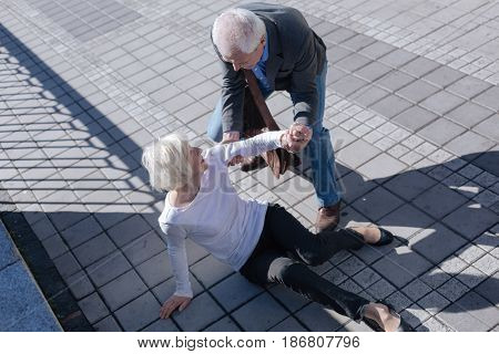 Do not afraid of falling down. Funny white-haired slim lady catching foot and receipting of relief from aged man who smiling