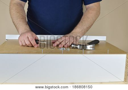 Man's hands on a drawer backside set on working table
