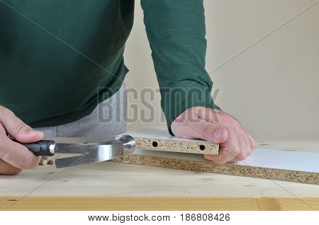 Hammering wooden dowels in to a particle board on working table