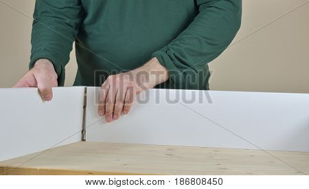 Man attaching two sides of a drawer set on working table