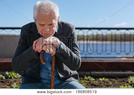 Do not back to past. Clever, thoughtful white-haired pensioner remembering his wife and mulling over his future while sitting on the bench