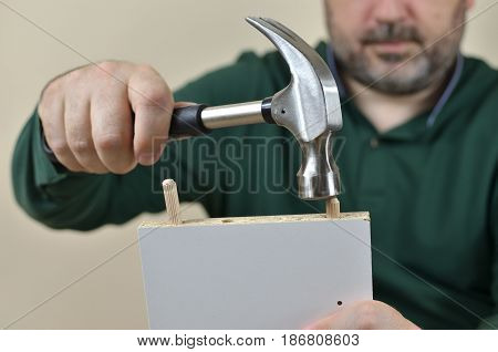Man installing wooden dowels in to a particle board with hammer