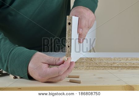 Man inserting wooden dowels into a particle board of a new cabinet