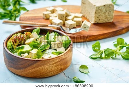 Green vegan salad with tofu avocado and cucumber. Love for a healthy vegan food concept