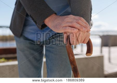 Waiting for my love. Aging concentrated old pensioner standing on the promenade and putting his hands on the stick and relaxing