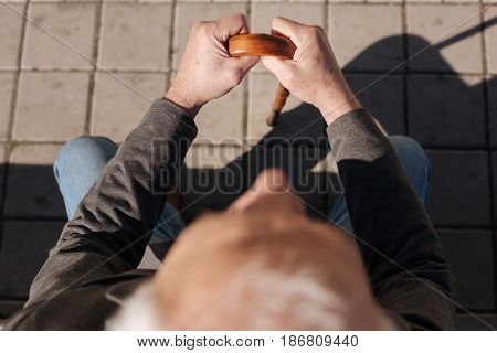 Everyone right to rest. Calm tired tidy man sitting on the bench resting and basking in the sun