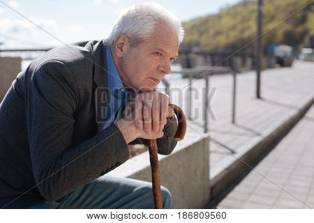 Solitary existence. Middle-aged concentrated sad man holding hands on the stick and lying down head on the hands while listening to classical music