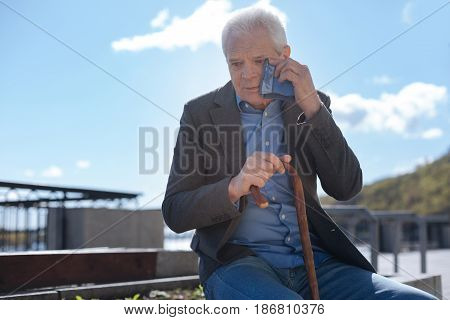 So terrible to have pain every time. Pleasant aged tired pensioner holding stick in one hand and trying to relax while suffering from ears ache