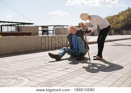 Do not refuse to help people. Diseased smiling pleasant man standing up using his stick while polite woman helping this man