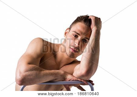 Naked young man sitting and resting on chair's back, head on one arm looking away