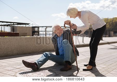 Respect old age. Shy aged ill man sitting on the ground and smiling while decent woman worrying about this man