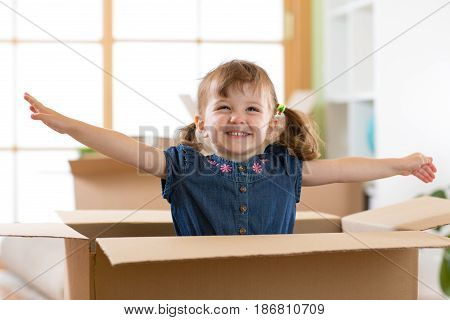 Laughing child girl sitting in cardboard boxe in her new home