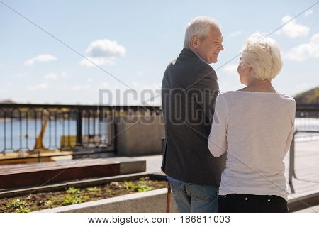 Love does not fade with time. Grey-headed glad enthusiastic man smiling and listening to his wife while aged women talking