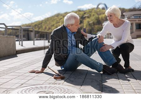 Lack of help. Upset diseased moody man staying on the ground felling knee ache while nice woman comforting him