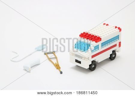 Toy ambulance car,  miniature drop, gibbs, and crutch on white background. Health, medicine, and cardiology concept.  Charity, health care, donation concept.