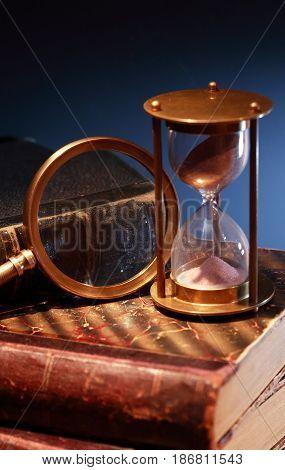 Vintage still life. Hourglass on old book against dark background