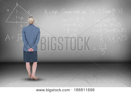 Businesswoman standing with hands behind back against grey room