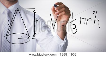 Mid section of businessman writing with marker against grey background
