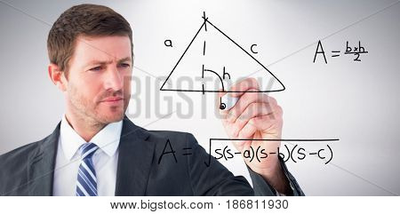Serious businessman writing with marker against grey background