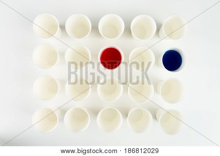 Top View Of Set Of Empty Plastic Cups And Cups With Red And Blue Paints