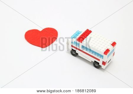 Toy ambulance car and abstract red heart on white background. Health, medicine, and cardiology concept.  Charity, health care, donation concept.