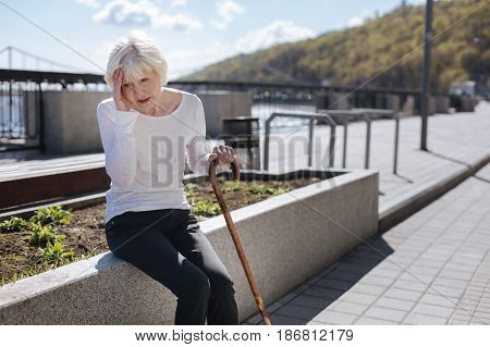 Uncontrolled process in our body. Aging sad tired woman holding hand on the head while expressing negative emotions and resting on the bench
